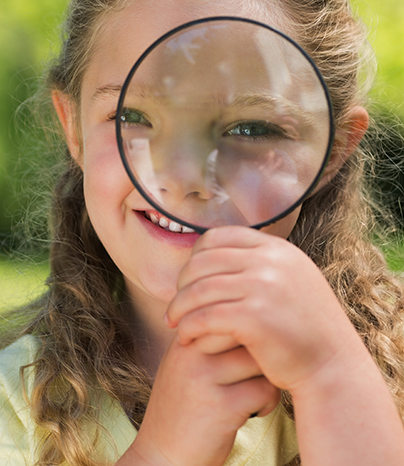 Girl looking through a looking glass